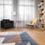 Dywan w geometryczne kształty leżący w salonie w mieszkaniu w kamienicy z 1936 roku projektu Loft Kolasiński