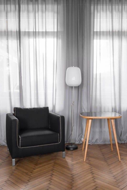 Czarny fotel, biała stojąca lampa i drewniany stolik