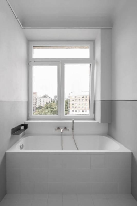 Łazienka z białą wanną i widokiem na Warszawę w mieszkaniu z 1936 roku