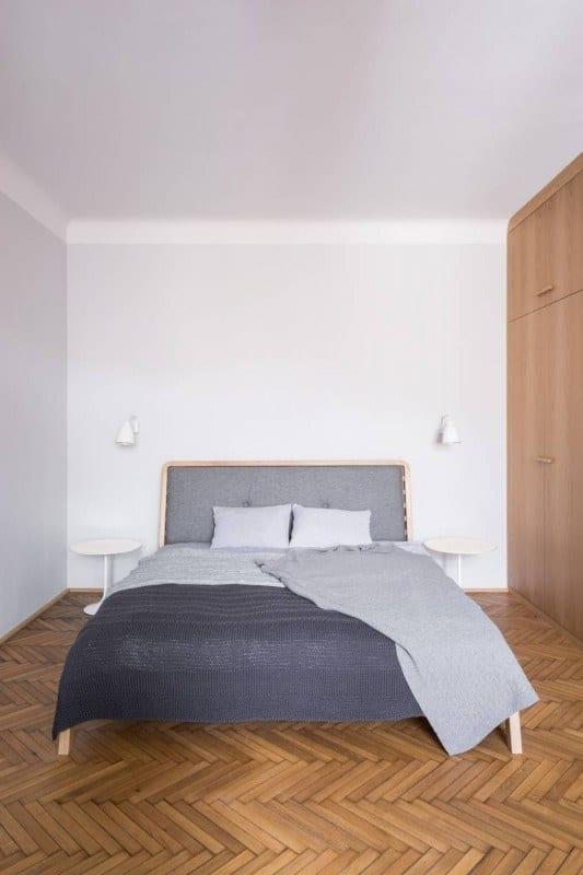 Duże łózko z drewnianą ramą w sypialni w kamienicy