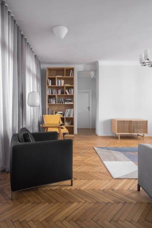 Salon z drewnianym parkietem w mieszkaniu w kamienicy projektu Loft Kolasiński
