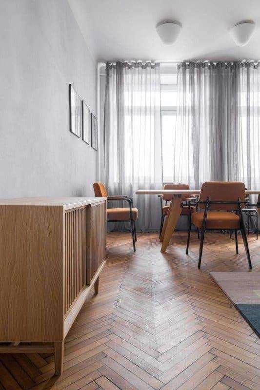 Komoda i stół z krzesłami w salonie w mieszkaniu w kamienicy
