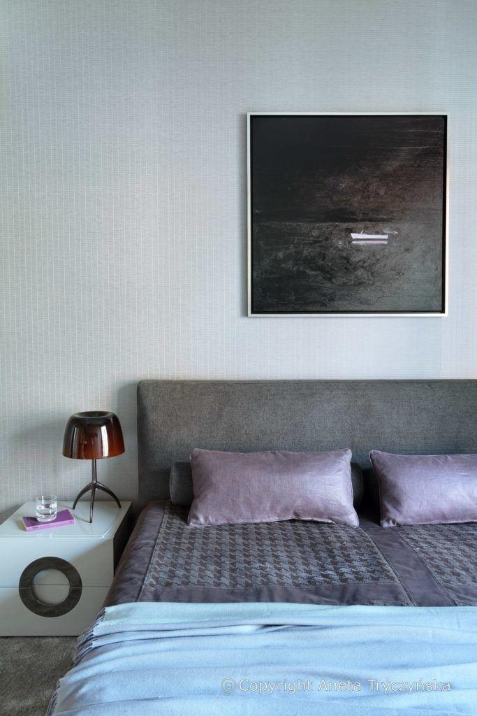 Sypialnia z szarym łóżkiem w luksusowym apartamencie na Muranowie projektu Taff Architekci