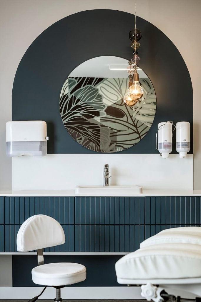 Okrągłe lustro i zielona komoda w SPA znajdującym się w Lush Life w Turku