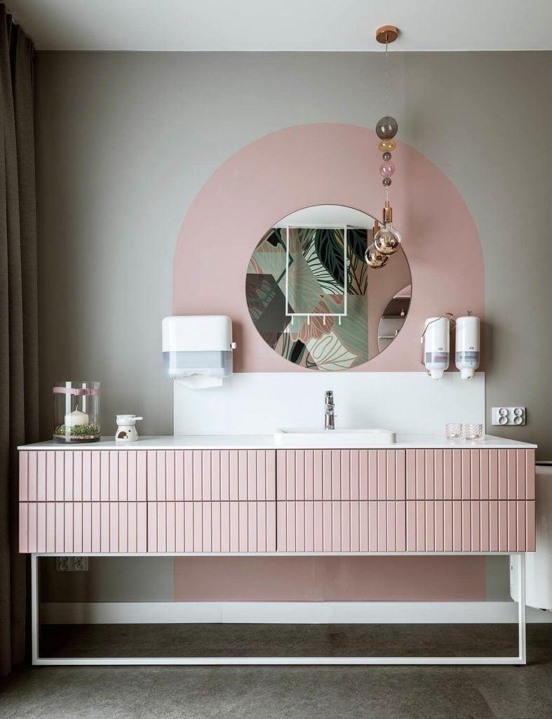 Piękna, różowa komoda o okrągłe lustro zawieszone na ścianie
