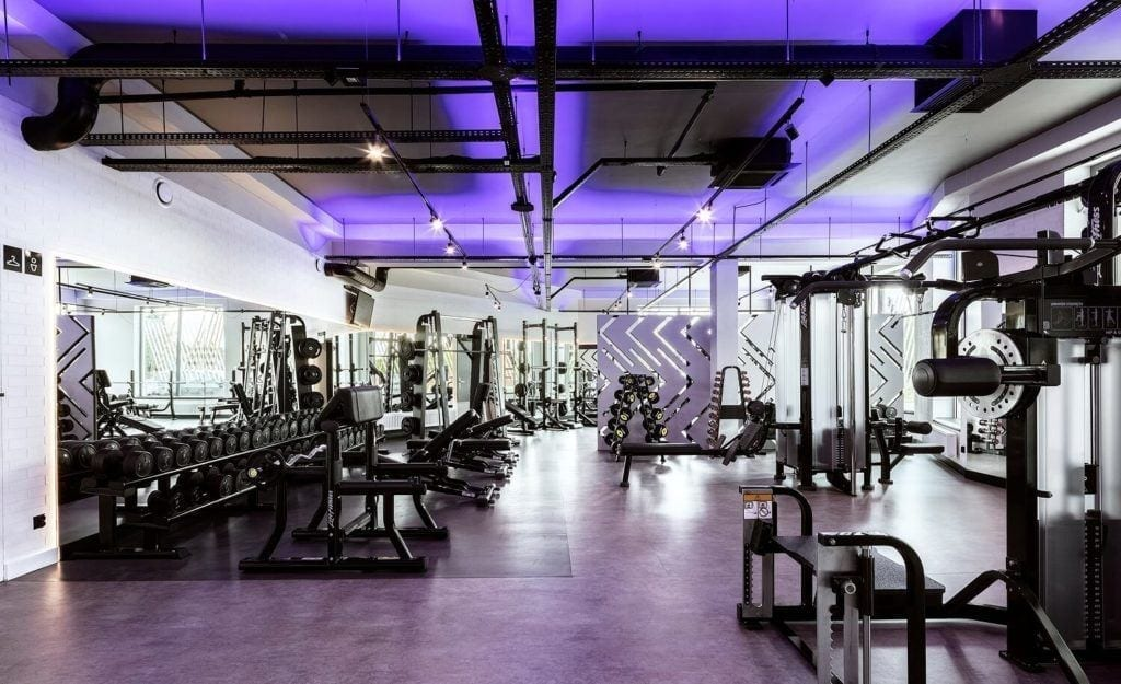 Wnętrze siłowni Lush Life podświetlone na fioletowo