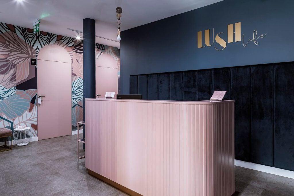 Recepcja z różą ladą i niebieską ścianą w siłowni i SPA Lush Life w Turku