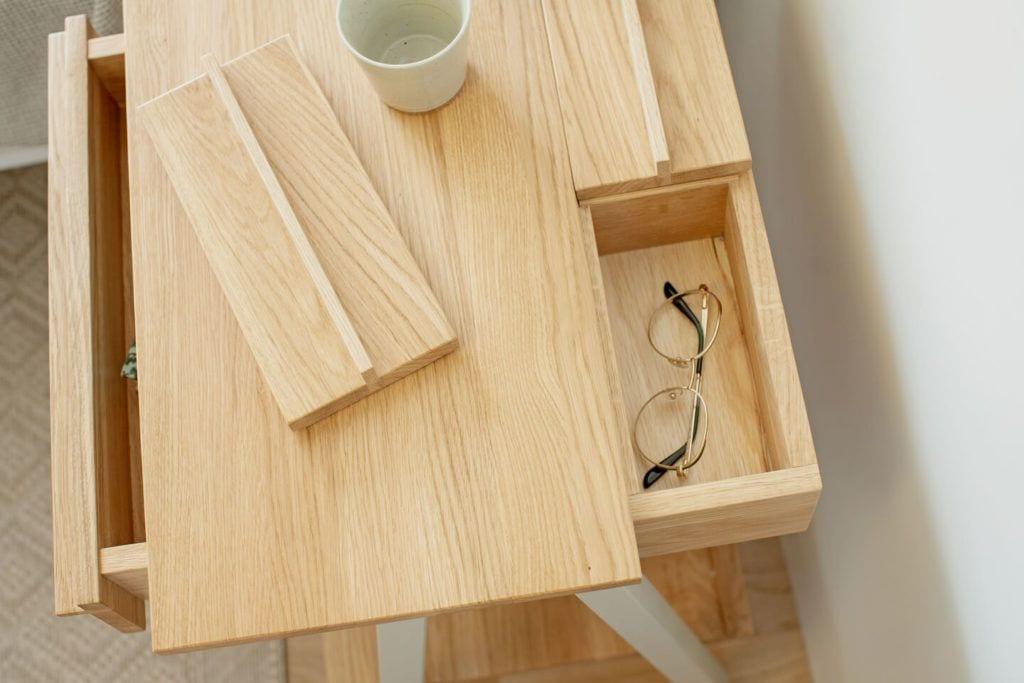 Szafka nocna troost z otwartą szufladą w której są schowane okulary