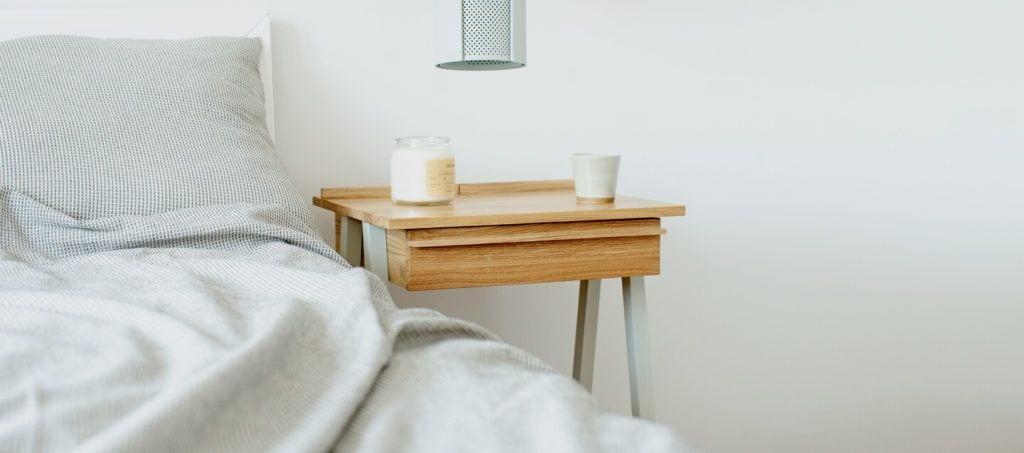 Szafka nocna troost z białymi nogami stojąca pod ścianą przy dużym łóżku