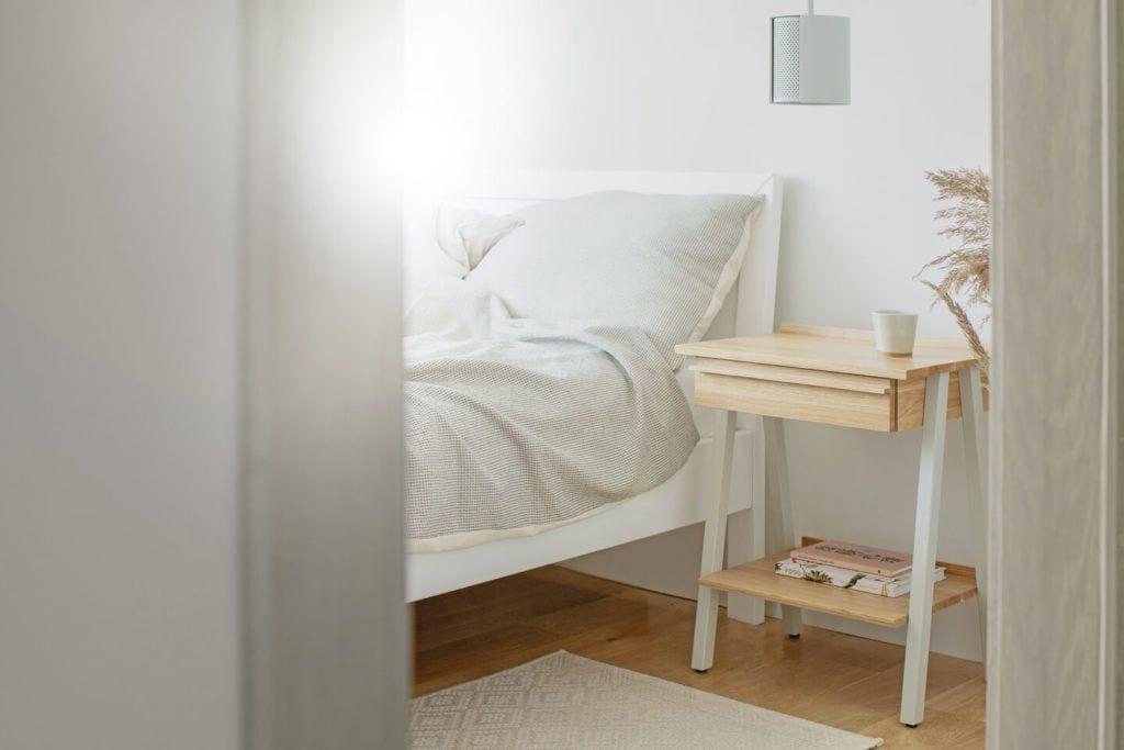 Szafka nocna troost stojąca przy białym łóżku z jasną pościelą