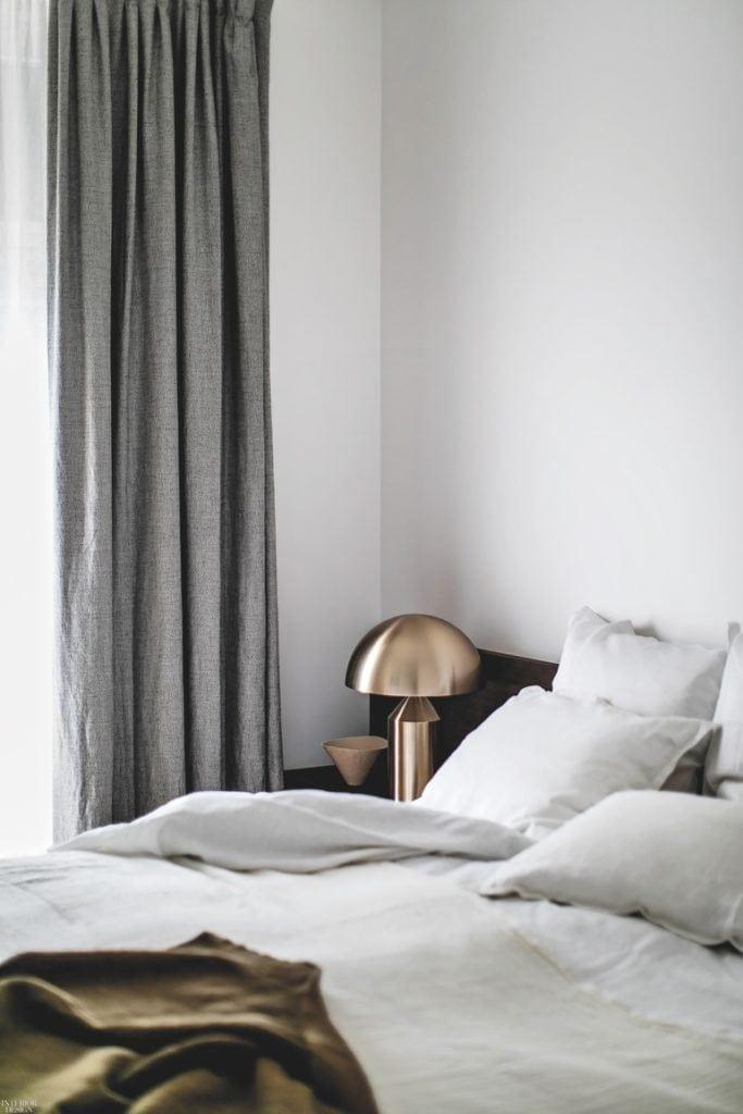 Piękna miedziana lampa stojąca przy łóżku w mieszkaniu