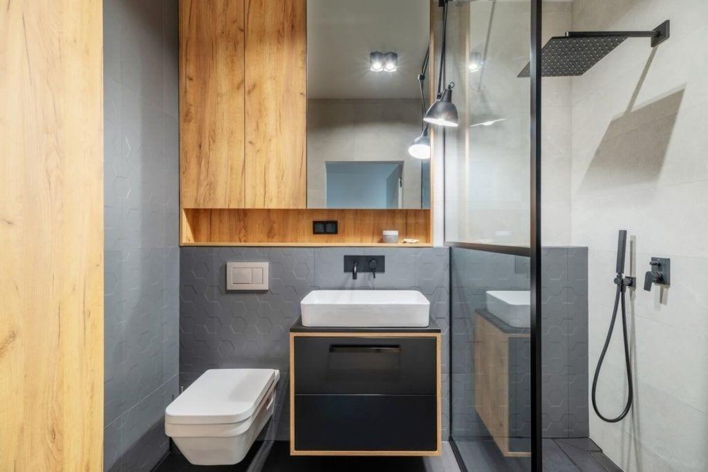 Łazienka z szarymi płytkami i drewnemw mieszkaniu z industrialnymi elementami projektu Deer Design