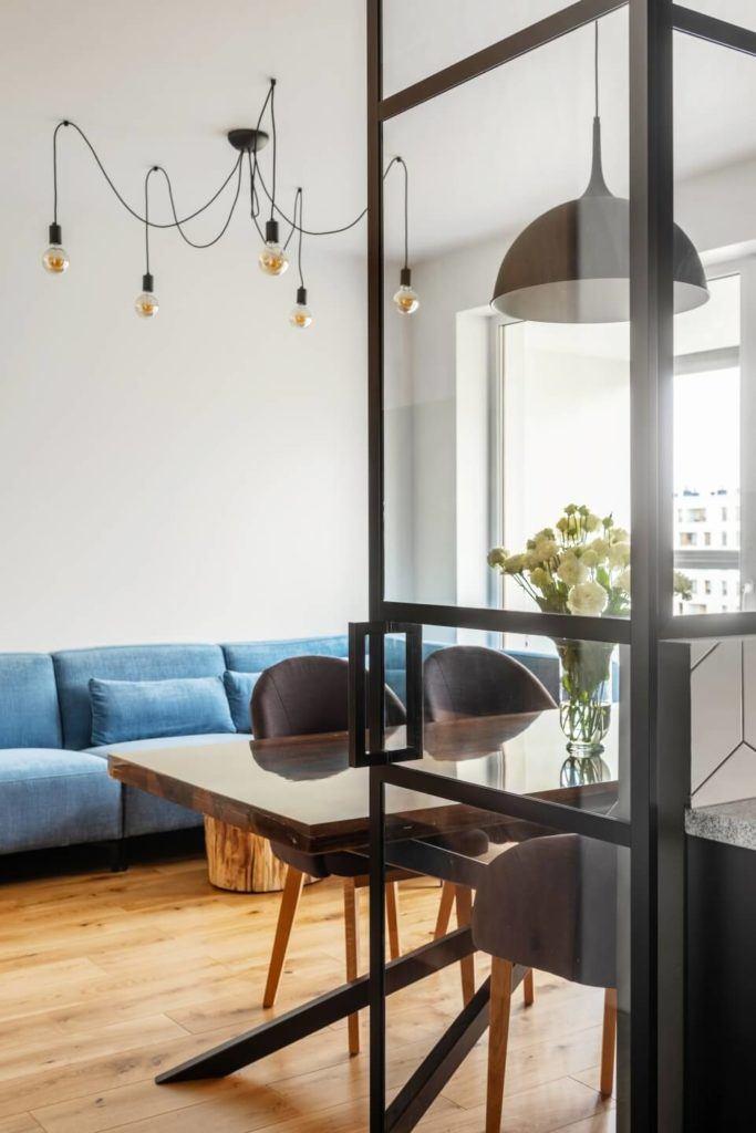 Niebieska sofaw mieszkaniu z industrialnymi elementami projektu Deer Design
