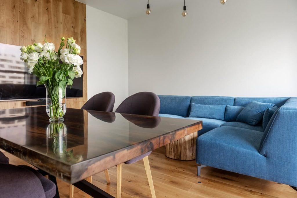 Drewniany stół w saloniew mieszkaniu z industrialnymi elementami projektu Deer Design