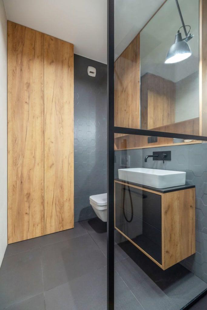 Szara łazienkaw mieszkaniu z industrialnymi elementami projektu Deer Design