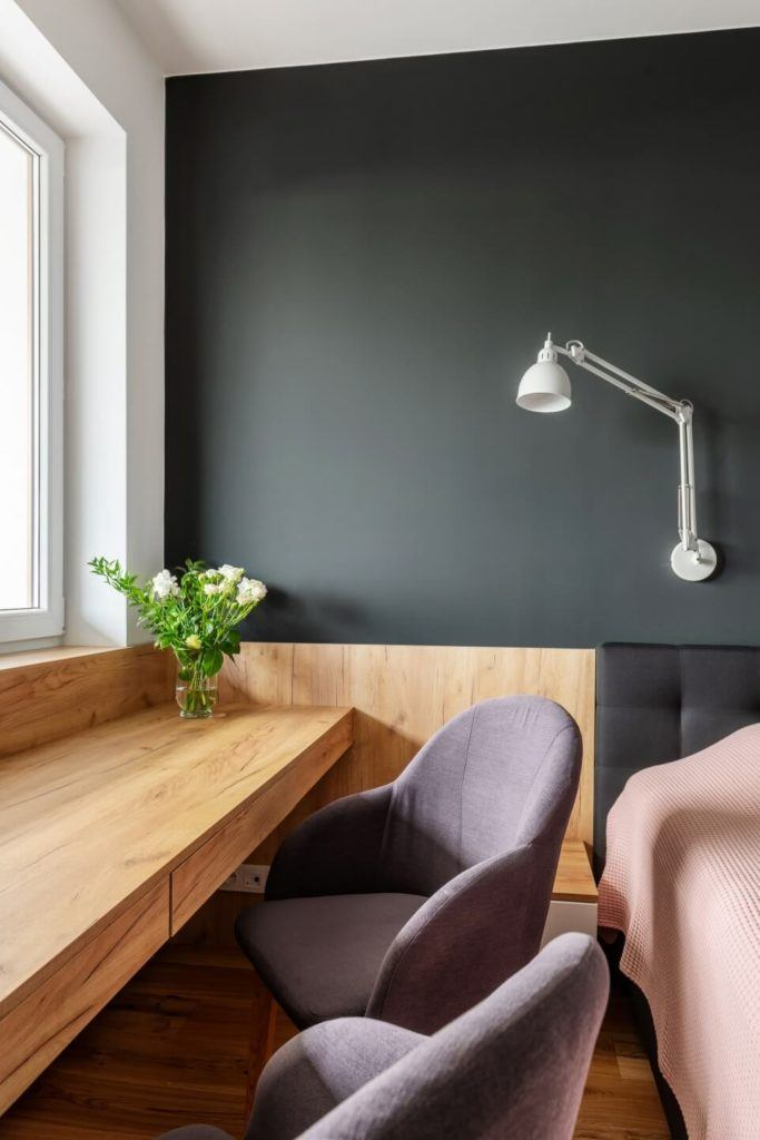 Sypialnia z ciemną ścianąw mieszkaniu z industrialnymi elementami projektu Deer Design