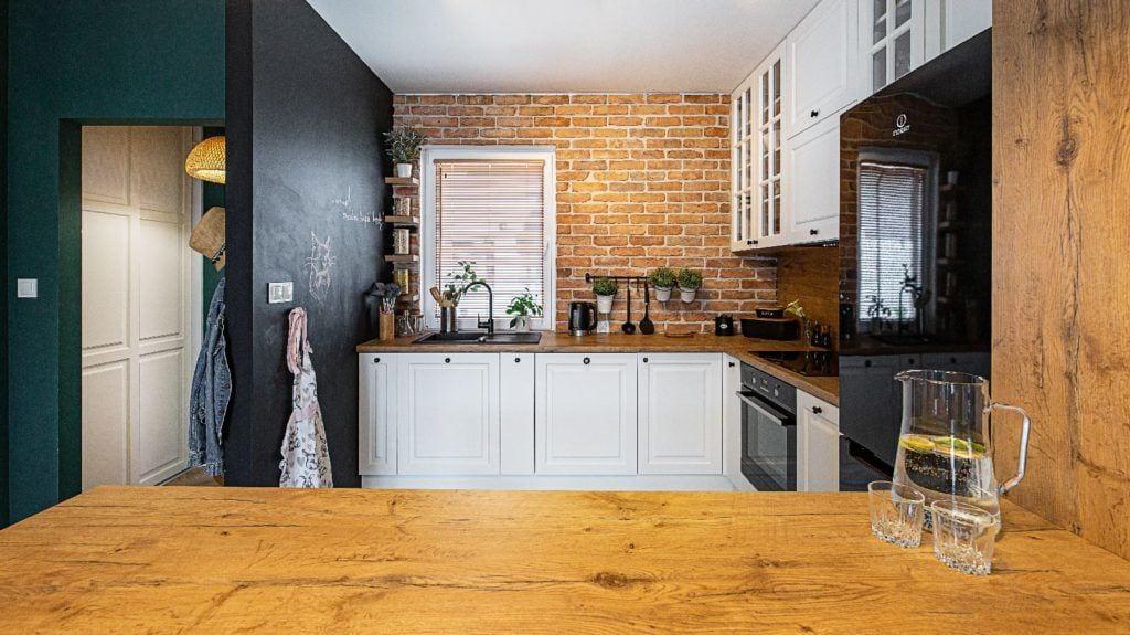 Kuchnia z jasnymi meblami i ściana z cegłą projektu pracowni Dobry Układ