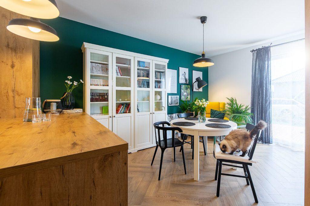 Salon z zieloną ścianą i drewnianą podłogą projektu pracowni Dobry Układ