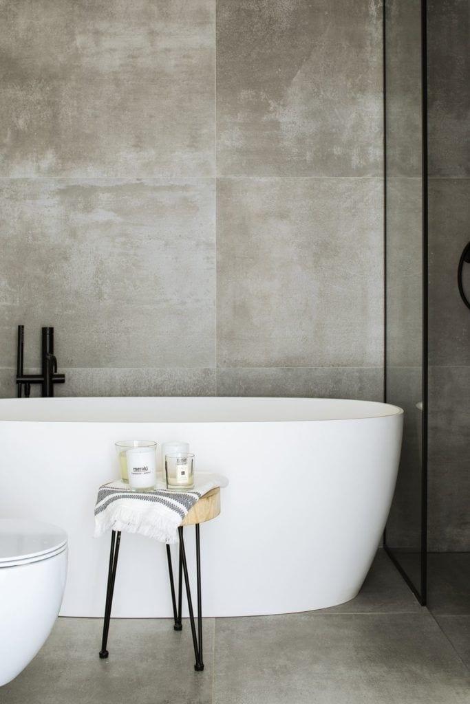 Biała wanna w szarej łazience w mieszkaniu na Żoliborzu projektu pracowni MADAMA