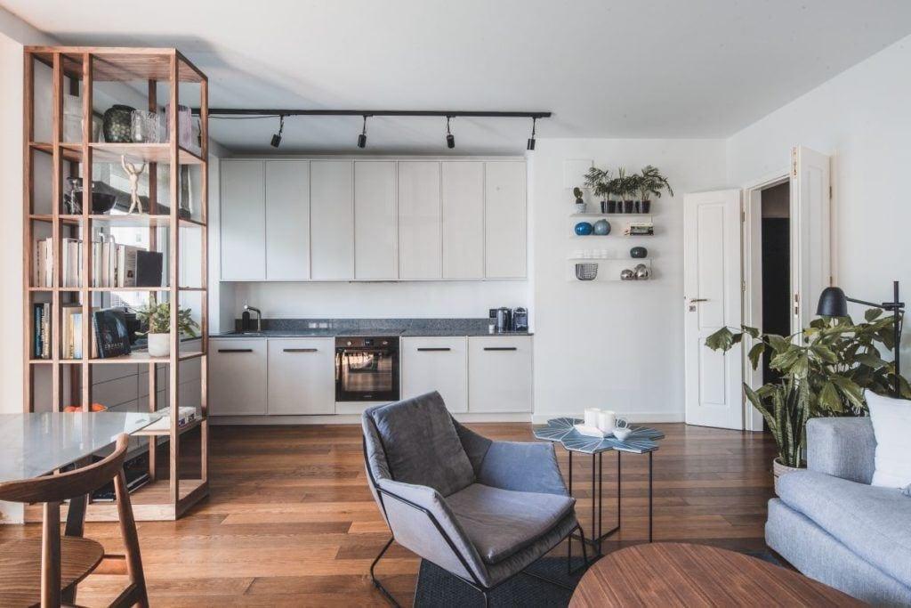 Salon połączony z kuchnią - białe meble i brązowa podłoga