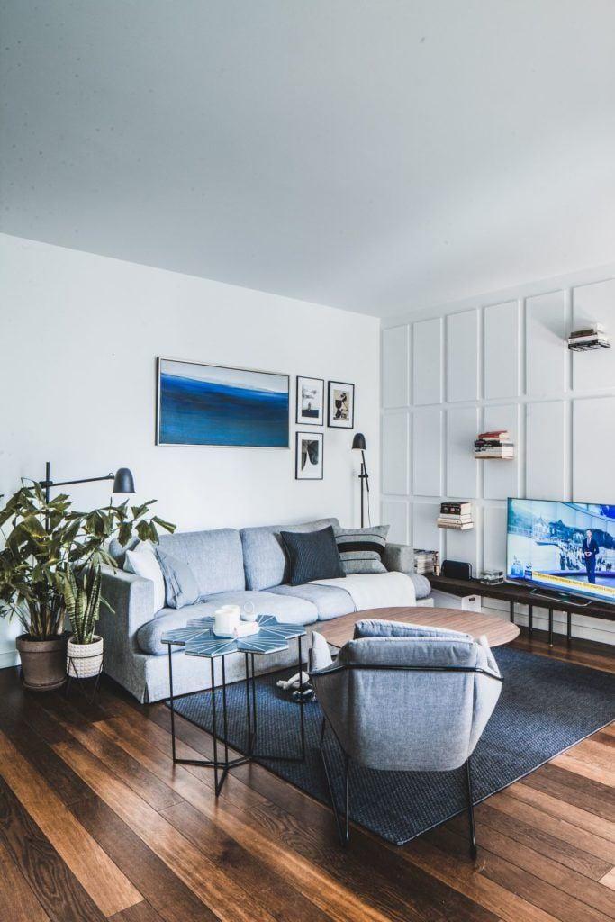 Jasny salon z obrazem na ścianie w przytulnym apartamencie projektu Taff Architekci