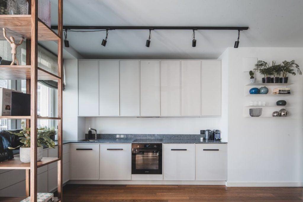 Kuchnia z białymi frontami w przytulnym apartamencie projektu Taff Architekci