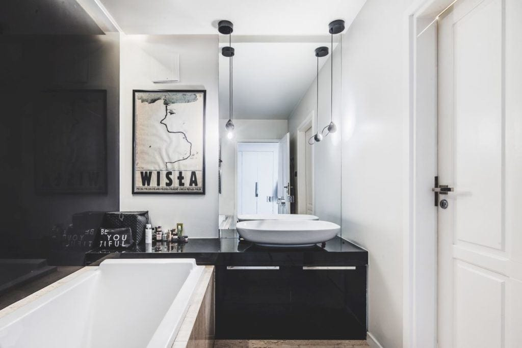 Jasna łazienka z plakatem na ścianie w przytulnym apartamencie projektu Taff Architekci
