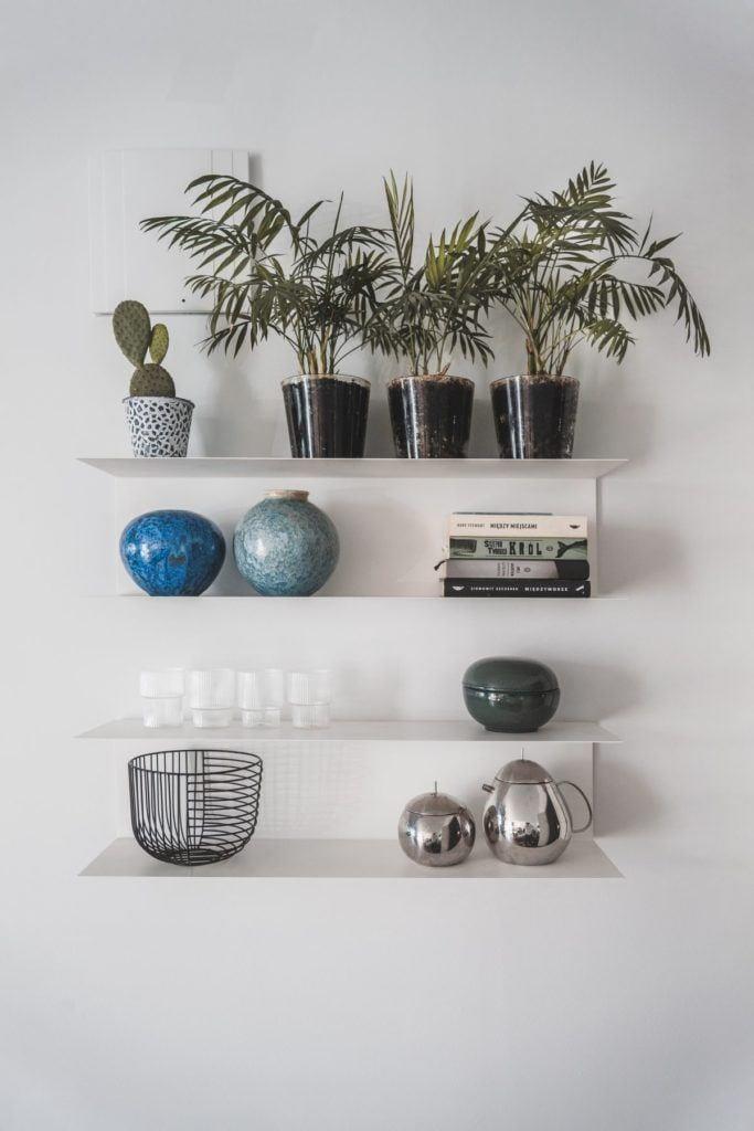 Przytulny apartament na Żoliborzu - dekoracje stojące na półkach na ścianie