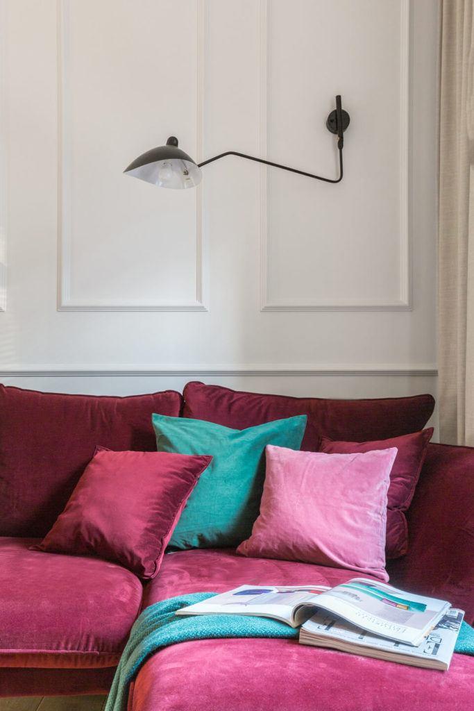 Salon z bordową sofą i kolorowymi poduszkami