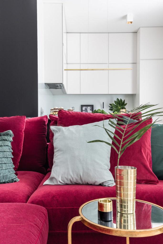 Czerwona sofa z białą poduszką