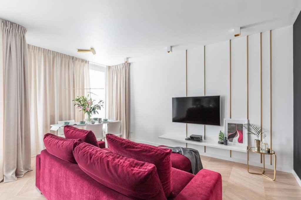 Bordowa sofa i telewizor na ścianie w salonie