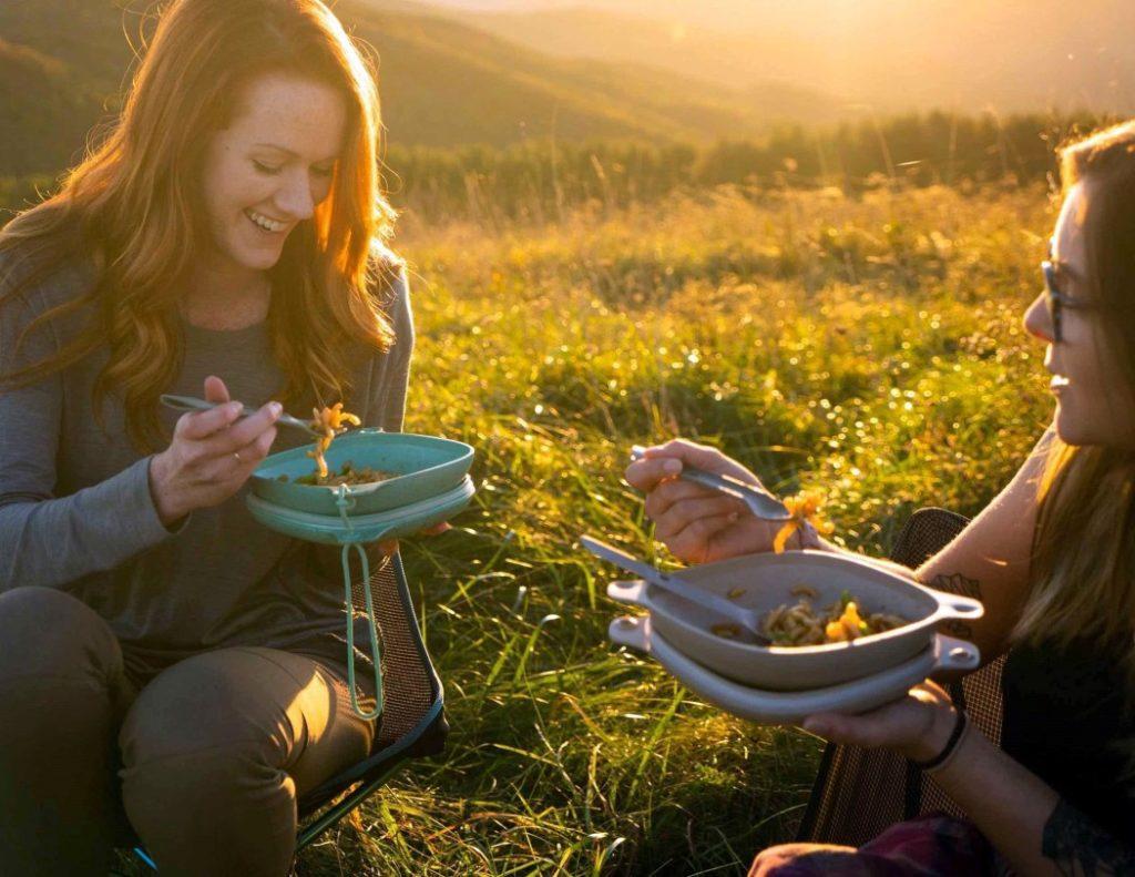 Dwie osoby jedzą posiłek siedząc na trawie