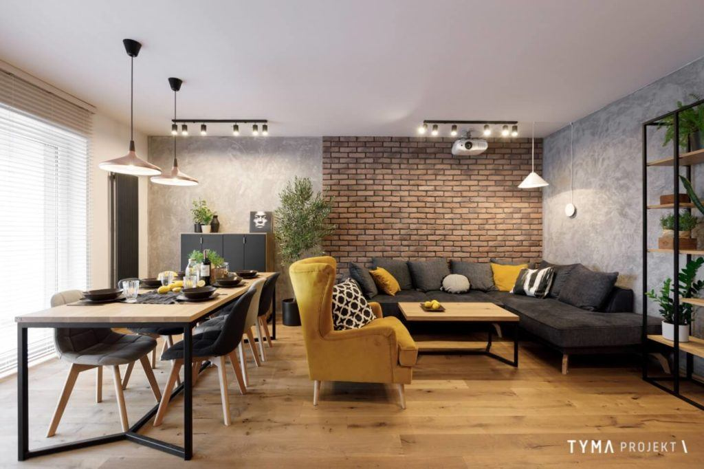 Salon z musztardowym fotelem w mieszkaniu projektu Tyma Projekt