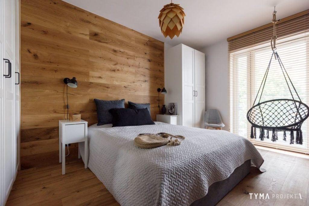 Sypialnia ze ścianą z drewna w mieszkaniu projektu Tyma Projekt