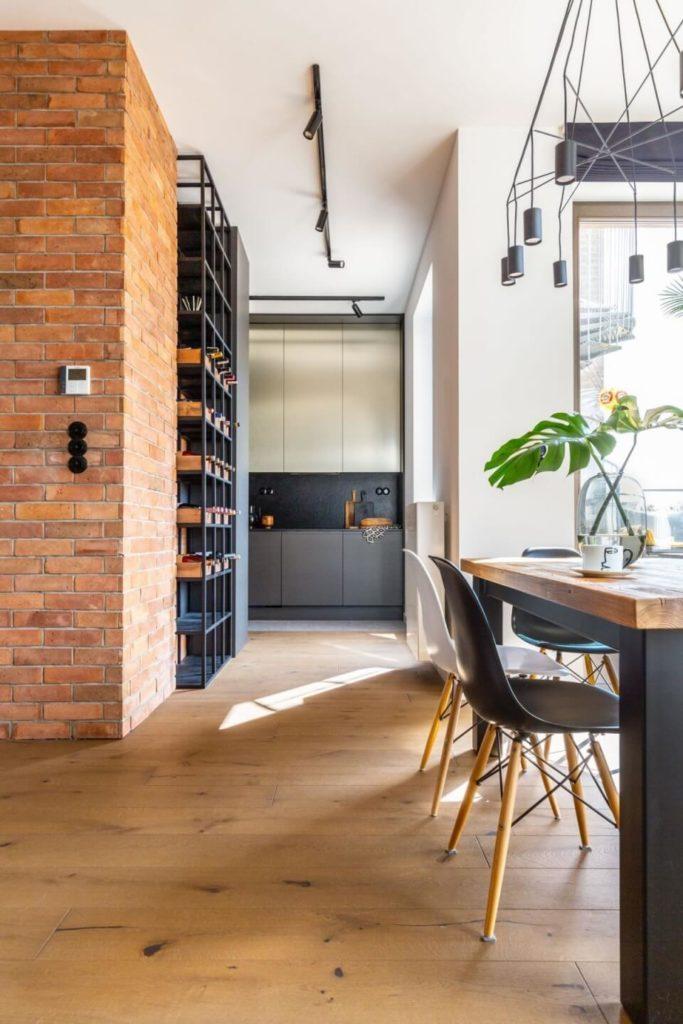 Decoroom i apartament na Bemowie z hygge w tle - jadalnia ze ścianą z cegły