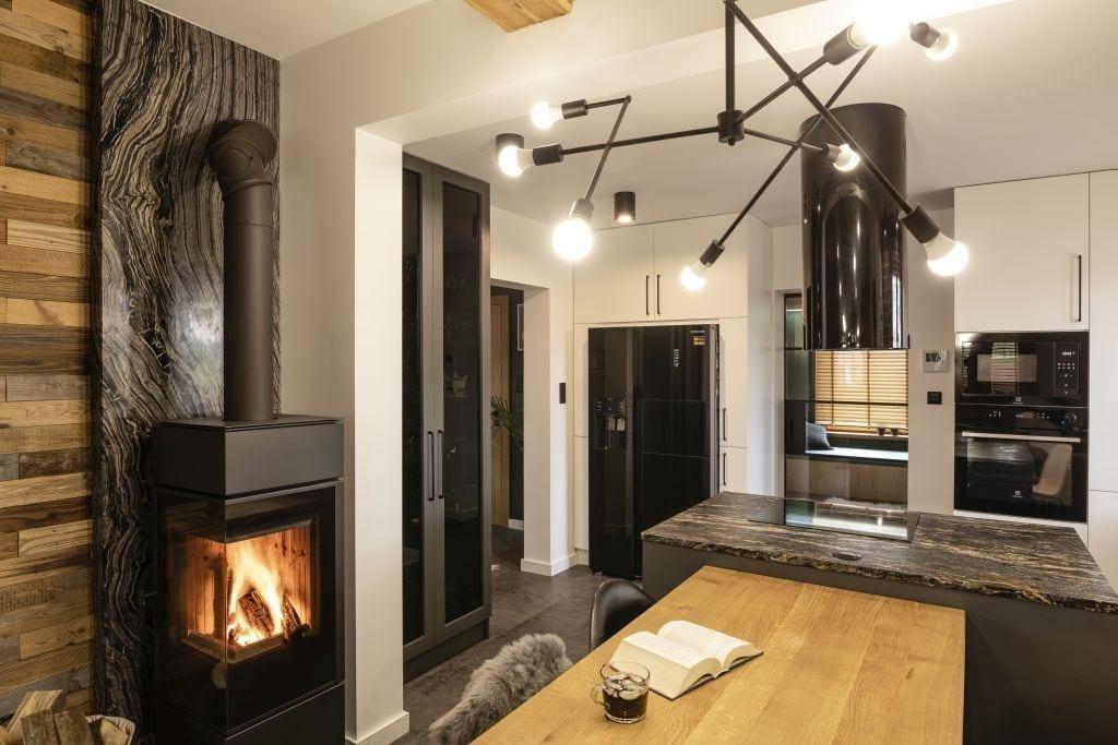 Lampa nad drewnianym stołem w jadalni w domu projektu pracowni Kaza Interior Design