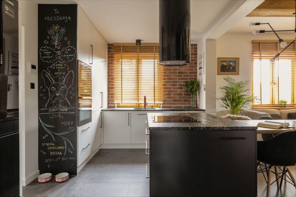 Kuchnia z wyspą w domu projektu pracowni Kaza Interior Design