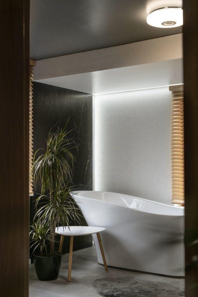 Zieleń i wolno stojąca wanna w łazience w domu projektu pracowni Kaza Interior Design