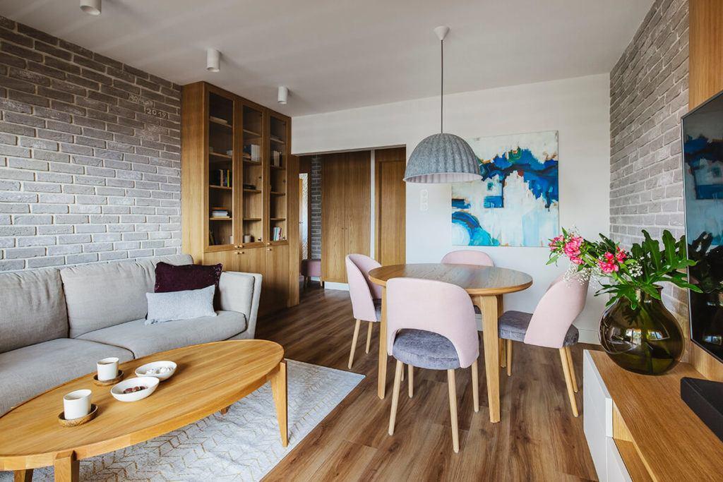 Mieszkanie na Helu projektu Kowalczyk-Gajda Studio Projektowe i stół w salonie z czterema różowymi krzesłami