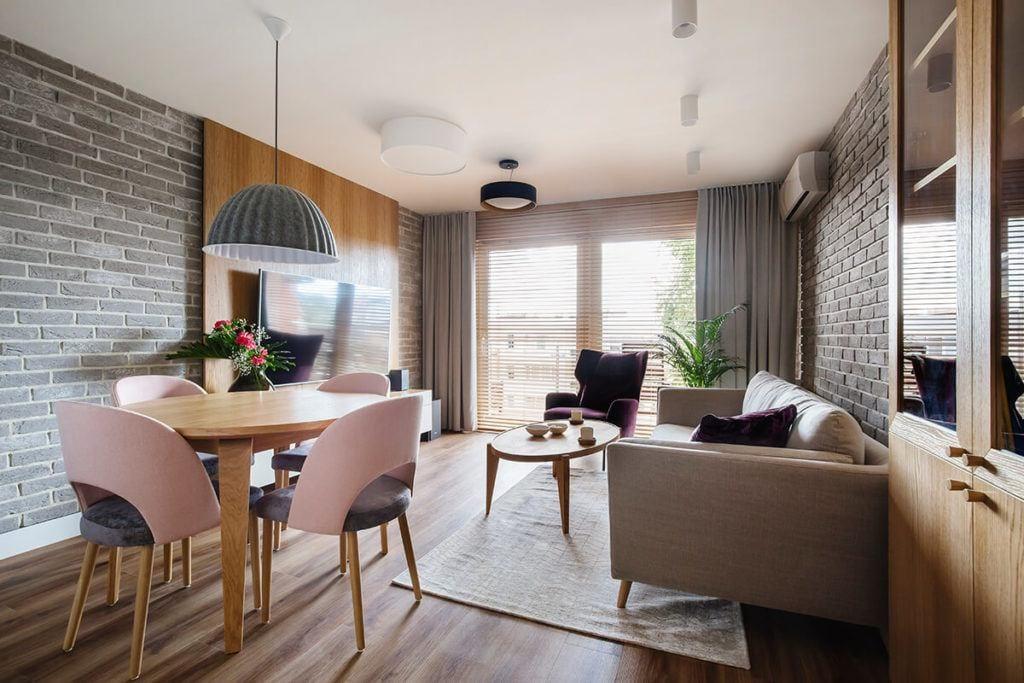 Mieszkanie na Helu projektu Kowalczyk-Gajda Studio Projektowe i duży salon z drewnianą podłogą