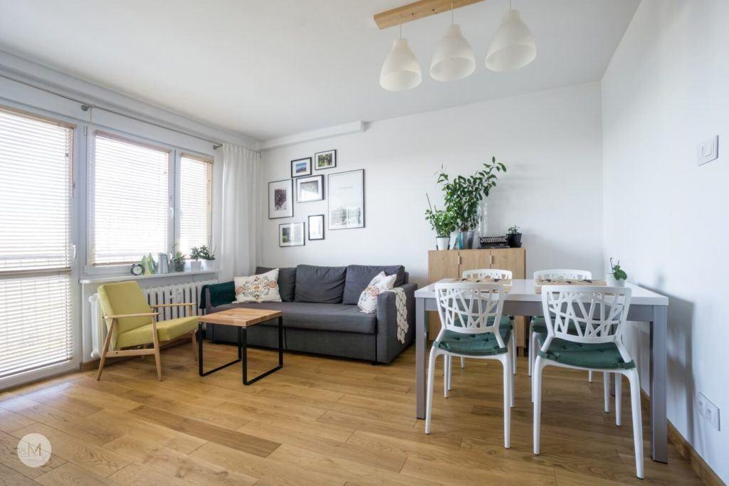 Kanapa i stół z krzesłami w salonie w mieszkaniu w Pabianicach projektu pracowni PROJEKT M