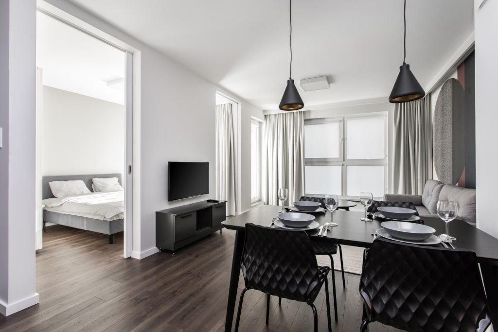 Pracownia Studio Poziom & salon Dekorian Home - minimalistyczny apartament w Gdańsku - foto Tomasz Nowicki Studio - stół w salonie