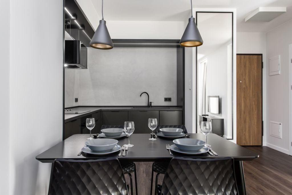 Pracownia Studio Poziom & salon Dekorian Home - minimalistyczny apartament w Gdańsku - foto Tomasz Nowicki Studio - czarny stół w salonie