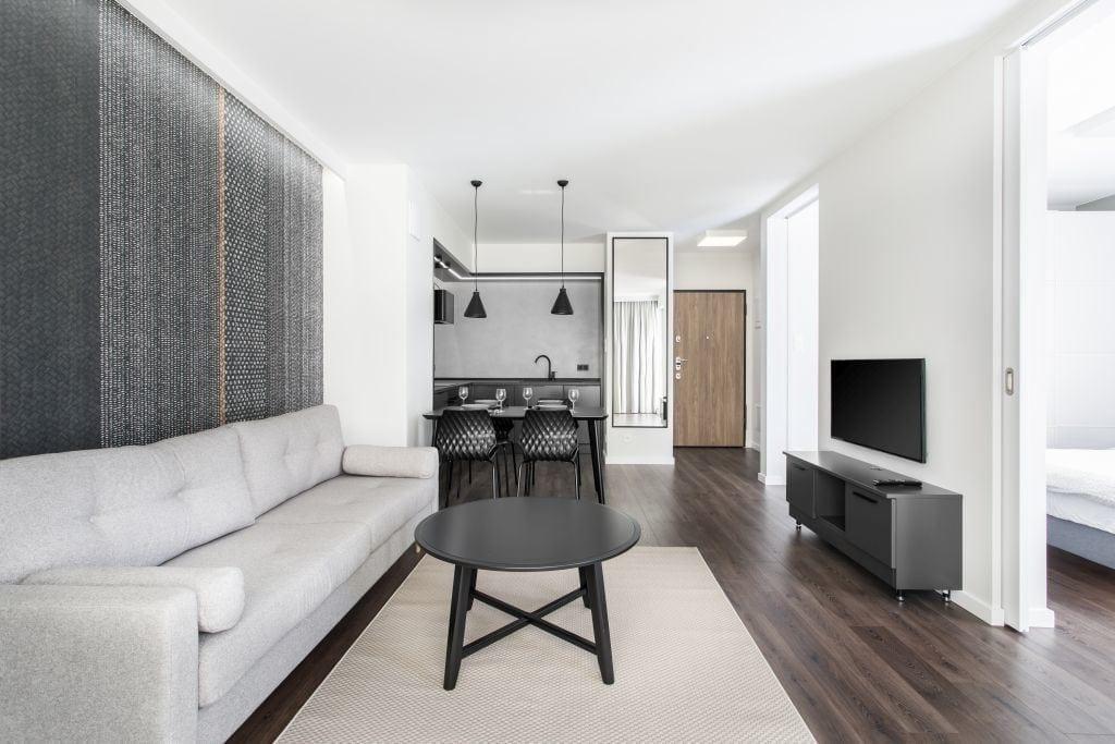 Pracownia Studio Poziom & salon Dekorian Home - minimalistyczny apartament w Gdańsku - foto Tomasz Nowicki Studio - beżowy dywan w salonie