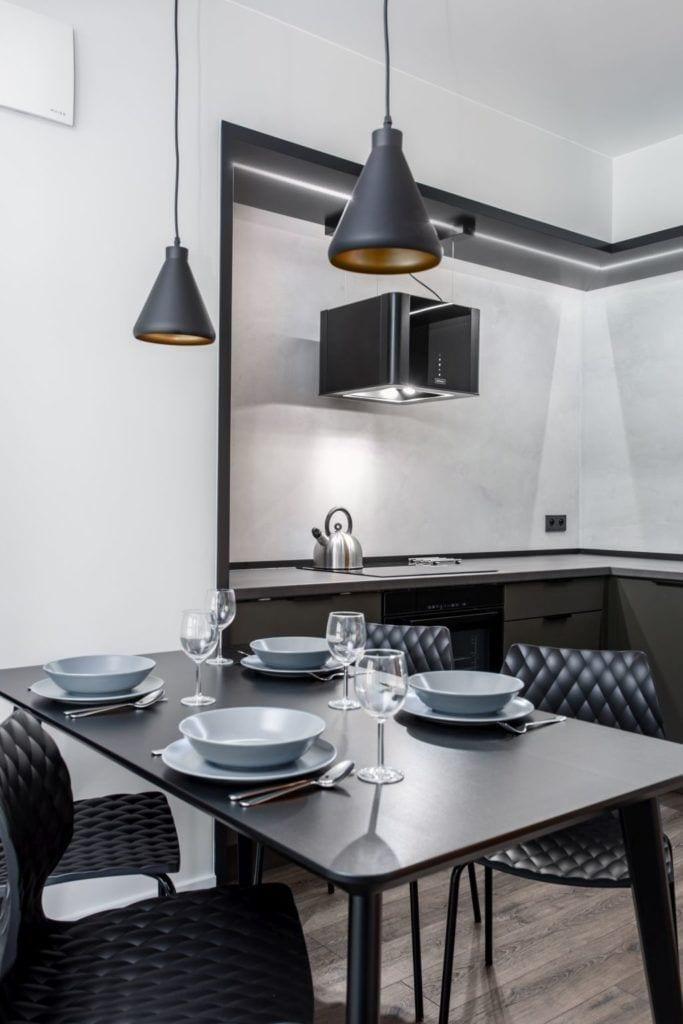 Pracownia Studio Poziom & salon Dekorian Home - minimalistyczny apartament w Gdańsku - foto Tomasz Nowicki Studio - czarny stół z zastawą