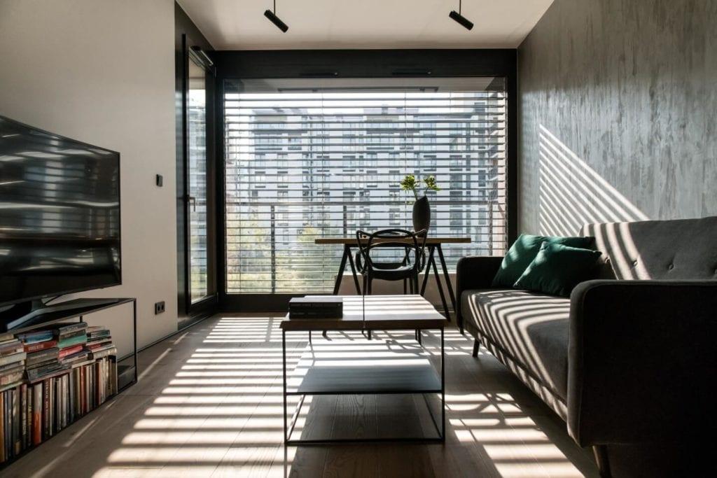 50-metrowe mieszkanie na warszawskim Żoliborzu projektu Deer Design - sofa, stolik i stół w salonie