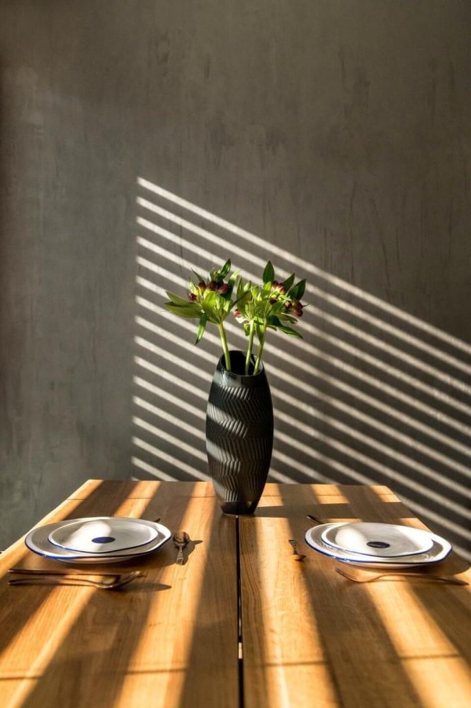 50-metrowe mieszkanie na warszawskim Żoliborzu projektu Deer Design - drewniany stół z dwoma talerzami