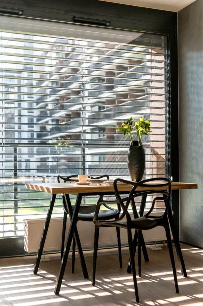 50-metrowe mieszkanie na warszawskim Żoliborzu projektu Deer Design - drewniany stół stojący pod oknem