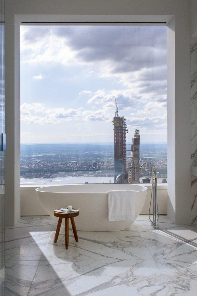 Apartament przy 432 Park Avenue w Nowym Yorku projekt John Beckmann - Axis Mundi - biało-czarny korytarz - łazienka z widokiem na Manhattan