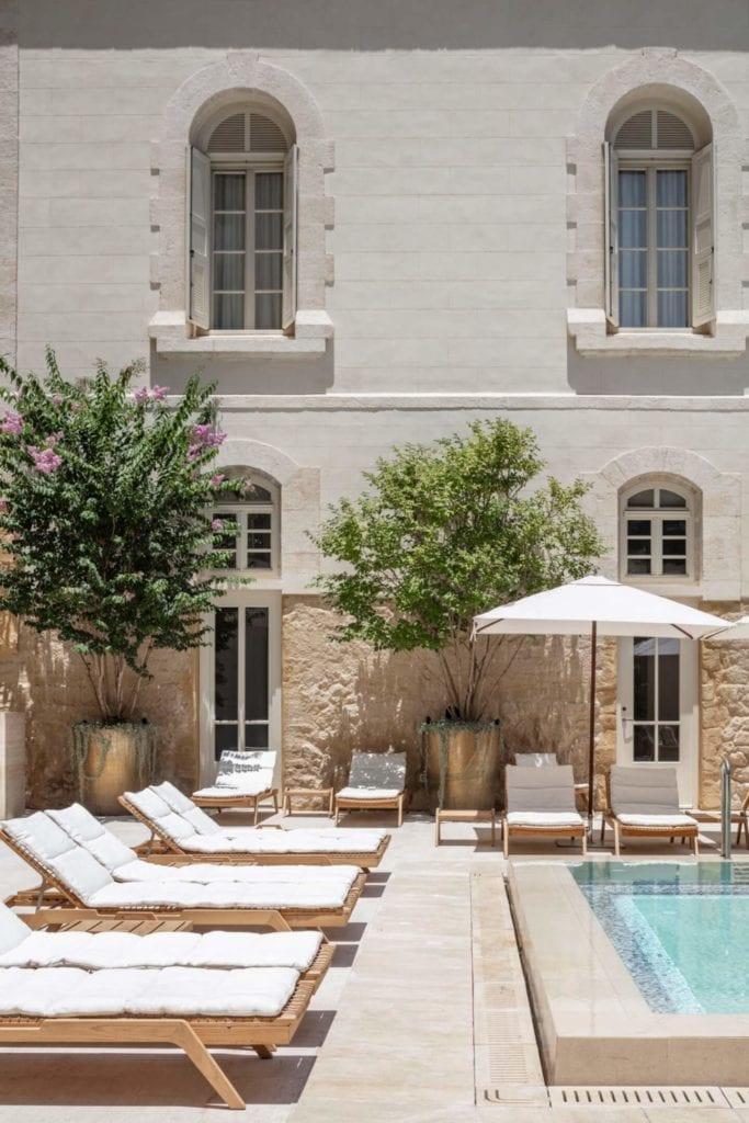 John Pawson i projekt Jaffa Hotel Residences - zdjęcia Amit Geron - leżaki przy basenie hotelowym